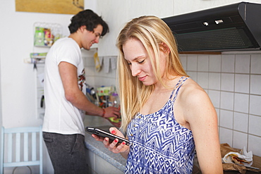 Young couple in the kitchen, woman on her mobile