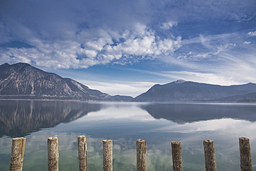 Wooden poles on the shore of lake Walchensee at low tide overlooking the Herzogstand, Walchensee, Alps, Bavaria, Germany