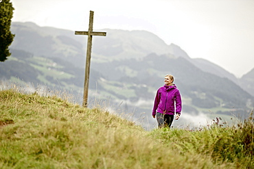 Woman hiking in the mountains, Chiemgau, Bavaria, Germany