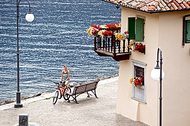 Young woman having a break with her bike at a bench near a lake, Lake Garda, Italy
