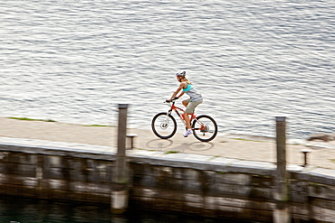 Young woman riding with her bike on a port at a lake, Lake Garda, Italy