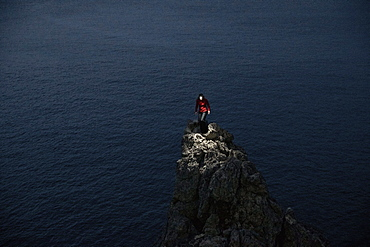 Young woman standing on a spiky rock at the sea, Mallorca, Spain