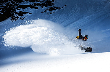 Young female snowboarder riding through deep powder snow in the mountains, Pitztal, Tyrol, Austria