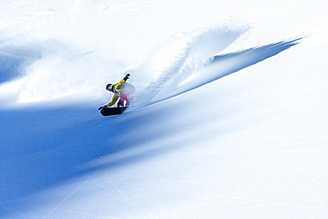 Young male snowboarder riding through deep powder snow in the mountains, Pitztal, Tyrol, Austria