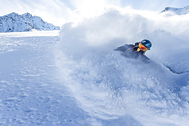 Young female freeskier riding through deep powder snow in the mountains, Pitztal, Tyrol, Austria