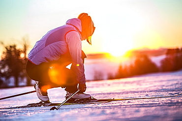 Young woman tying her shoes before cross-country skiing at sunset, Allgaeu, Bavaria, Germany