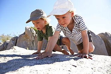 Two boys climbing over rocks, Kubu Island, Makgadikgadi Pans National Park, Botswana