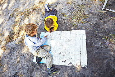 Two boys reading a map, Makgadikgadi Pans National Park, Botswana