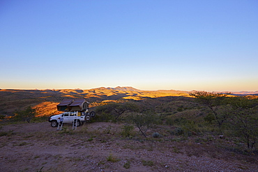 Off-road vehicle with roof top tent in sunrise, Gamsberg pass, Namibia