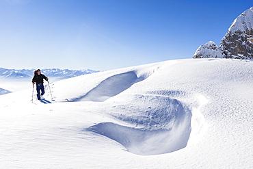 Snowshoe hiker, overlooking Riffl, Tennengebirge mountains, Salzburg, Austria