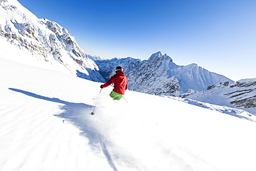 skier in deep powder snow, Zugspitze, overlooking Reintal Valley and Hochwanner, Upper Bavaria, Germany