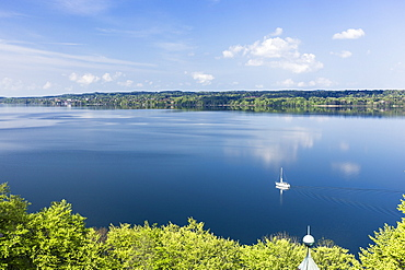 Sailing boat on Lake Starnberg in May, overlooking Tutzing, Bavaria, Germany