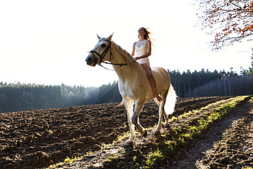 girl in white dress horseback-riding, Freising, Bavaria, Germany