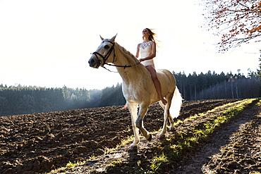 girl in white dress horseback-riding, Freising, Bavaria, Germany