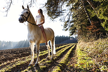 girl in a white dress riding her horse, Freising, Bavaria, Germany