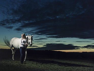 Girl standing next to her horse at dusk, Freising, Bavaria, Germany