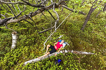 young woman resting in a moorland forest, Berg at Lake Starnberg, Upper Bavaria, Germany