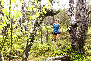 young woman running in a moorland forest, Berg at Lake Starnberg, Upper Bavaria, Germany