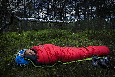 young woman in sleeping bag in a moorland forest, Berg at Lake Starnberg, Upper Bavaria, Germany