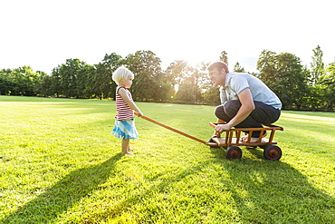 two-year-old girl pulling her father across the meadow, Speyer, Rheinland-Pfalz, Germany