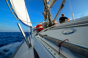 A young man sitting on the deck of a sailing yacht, Mallorca, Balearic Islands, Spain, Europe