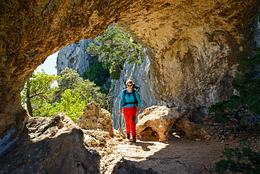 A young woman with trekking gear hiking through the rock arch Arcu su Feilau at the mountainous coast above the sea, Golfo di Orosei, Selvaggio Blu, Sardinia, Italy, Europe