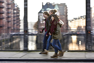 3 girls talking outside at Speicherstadt, Hamburg, Germany, Europe