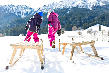 girl and boy pulling their sledges, Pfronten, Allgaeu, Bavaria, Germany