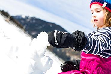 boy forming snowballs in winter, Pfronten, Allgaeu, Bavaria, Germany