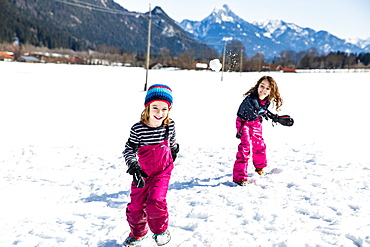 girl throwing a snowball towards a boy during a snowball fight in winter, Pfronten, Allgaeu, Bavaria, Germany