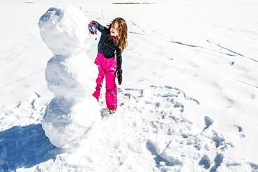 girl building a snowman in winter, Pfronten, Allgaeu, Bavaria, Germany