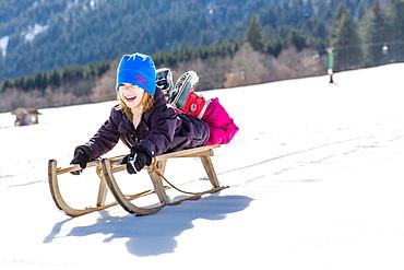 boy lying on his sled while sledging, Pfronten, Allgaeu, Bavaria, Germany