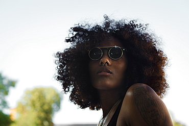 Portrait of a young afro-american woman with sunglasses and blue sky, Munich, Bavaria, Germany