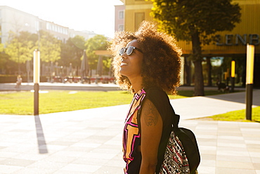 Young afro-american woman with backpack at Lenbachplatz, Munich, Bavaria, Germany