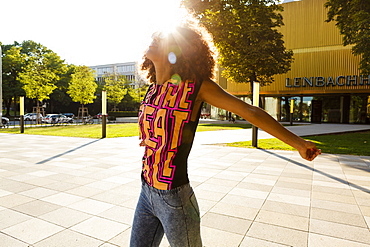 Young afro-american woman enjoying the sunshine at Lenbachplatz, Munich, Bavaria, Germany