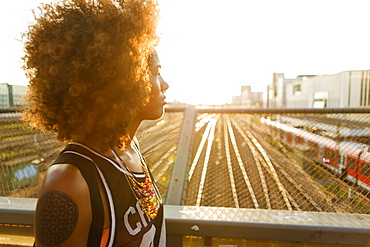 Young afro-american woman in backlight in urban scenery with tracks and station, Hackerbruecke Munich, Bavaria, Germany