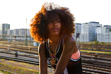 Young afro-american woman in modern urban scenery with train tracks, Hackerbruecke Munich, Bavaria, Germany