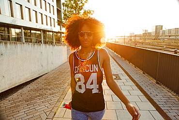 Young sportive and cool afro-american woman with glasses walking in backlight in modern urban scenery , Hackerbruecke, Munich, Bavaria, Germany