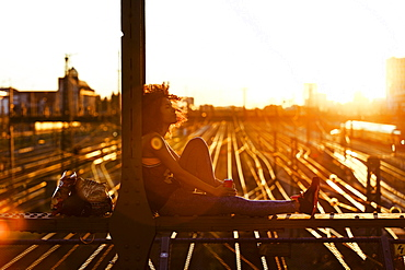 Young afro-american woman in evening light sitting on steel griders in urban scenery with tracks, Hackerbruecke Munich, Bavaria, Germany