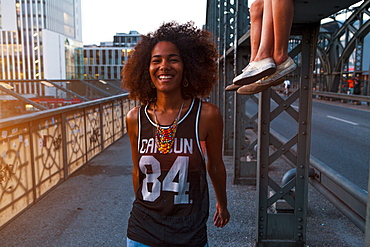 Young afro-american woman walking and laughing on a old steel bridge in urban scenery, Hackerbruecke bridge, Munich, Bavaria, Germany