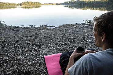 Young man sitting at a lake and drinking coffee, Freilassing, Bavaria, Germany