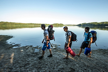 Three young male camper walking at a lake, Freilassing, Bavaria, Germany