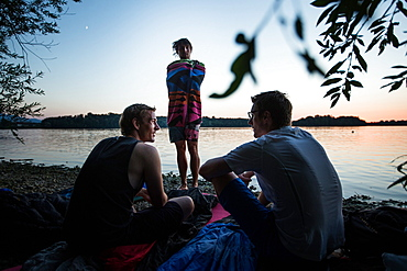 Three young men at a lake, Freilassing, Bavaria, Germany