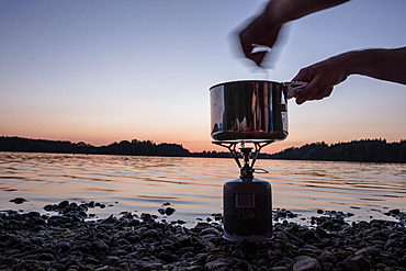 Person cooking with a camp stove at a lake at night, Freilassing, Bavaria, Germany