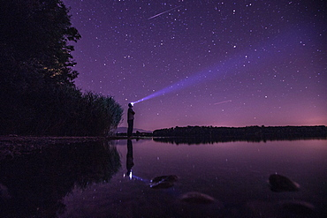 Young man standing at a lake and looking towards the stars, Freilassing, Bavaria, Germany