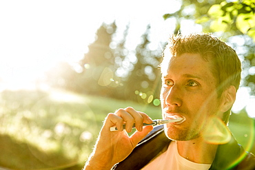 Young male camper brushing his teeth, Freilassing, Bavaria, Germany