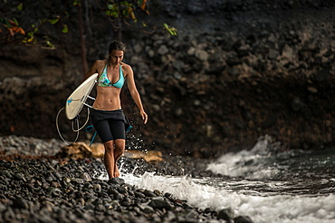 Young female surfer walking along the beach with her surfboard, Sao Tome, Sao Tome and Príncipe, Africa