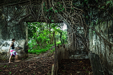 Young woman walking through an overgrown ruin, Sao Tome, Sao Tome and Principe, Africa