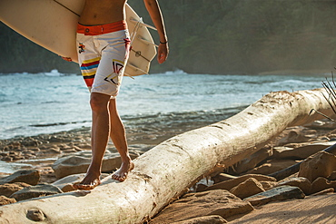 Young female surfer balancing over a trunk on the beach, Sao Tome, Sao Tome and Principe, Africa