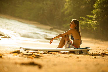 Young female surfer sitting on the beach with her surfboard, Sao Tome, Sao Tome and Principe, Africa